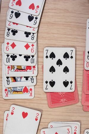 French playing cards stacked together in a solitaire. Solitaire game with cards, pastime with signs and cards with red backs and signs of spades and hearts
