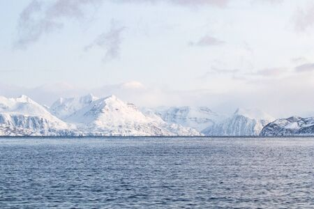 Arctic landscape in winter with snowy mountains and sea. Norwegian coasts and fjords seen from the boat in the open sea. Arctic polar north europe landscape with white snow and ice 免版税图像 - 143692958