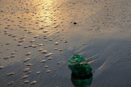 Green Plastic bottle on sea shore,sunset golden light,polluted ecosystem concept