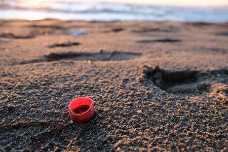 Red plastic bottle cork on sunset sea coast, polluted ecosystem,microplastics