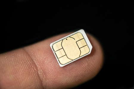 Isolated nano sim card on human finger over black background,hi tech smartphone