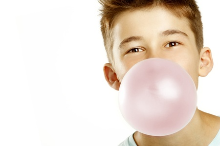 gums: boy make bubble with chew on white background