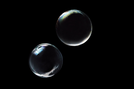 two soap bubbles on black background photo
