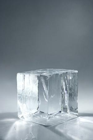 中立的な背景上の透明な大きな氷キューブ
