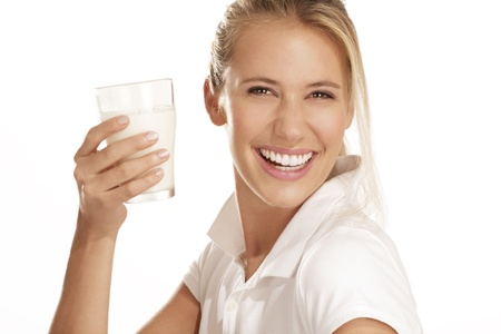 若い女性は白の背景に牛乳を飲む