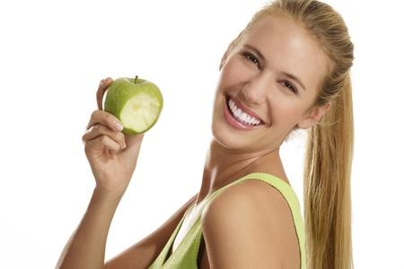 白い背景の上にリンゴを食べる若い女性