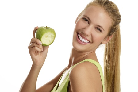 young woman eating an apple on white background