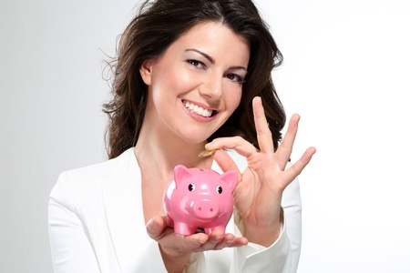 Young beautiful woman standing with piggy bank money box on white Stock Photo - 17643927
