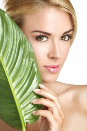 fresh face: beauty blonde young woman with a green leaf on white  Stock Photo