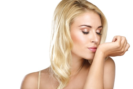 Beautiful blonde young woman smell his perfume on white photo