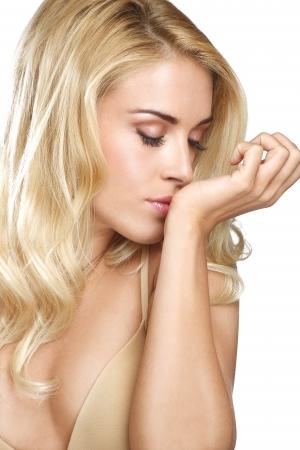 olfato: Joven y bella mujer rubia oler su perfume en blanco