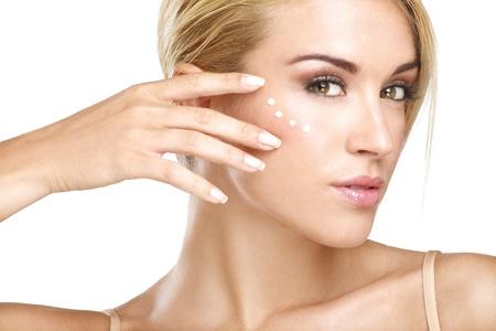 joven y hermosa aplicación de crema en su piel en blanco
