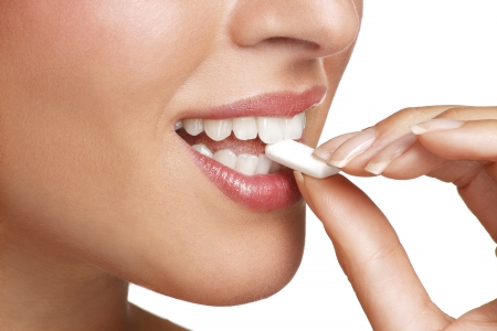 goma de mascar: cerca de una hermosa chica disfrutando de un caramelo en blanco Foto de archivo