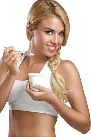 nutrici�n: hermosa mujer comiendo yogur fresco para el desayuno en blanco