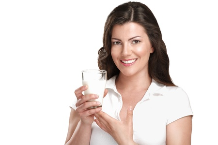 pretty brunette woman: young beautiful woman drink a glass of milk on white