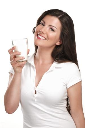 joven y bella mujer de beber un vaso de leche en blanco Foto de archivo