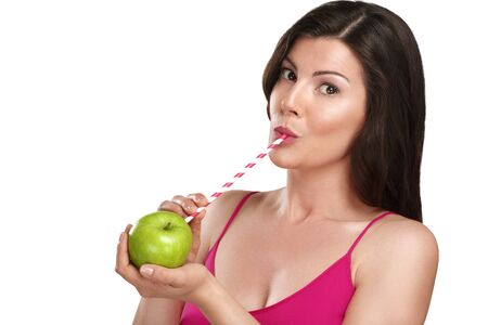 Top up on vitamin c for beautiful young woman drinking juice direct from an orange fruit using a straw on white photo
