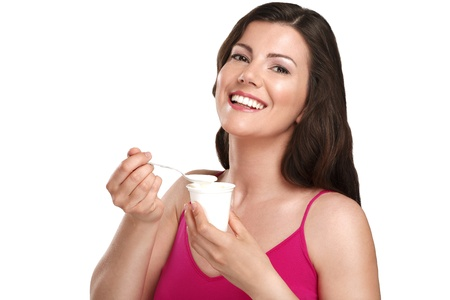 young beautiful smiling woman eating fresh yogurt on white