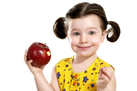 pretty child holding a red apple in her hands on white photo
