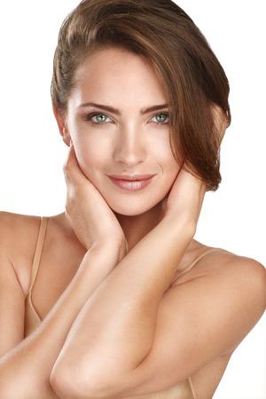 joven y bella modelo posando cerca de la piel perfecta en blanco Foto de archivo