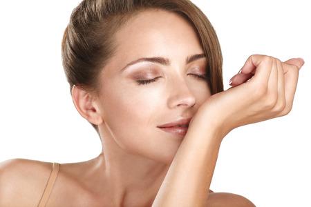 beautiful brunette female model smelling her perfume on white