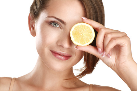 Woman beauty concept with fruits slices over eyes on white Archivio Fotografico