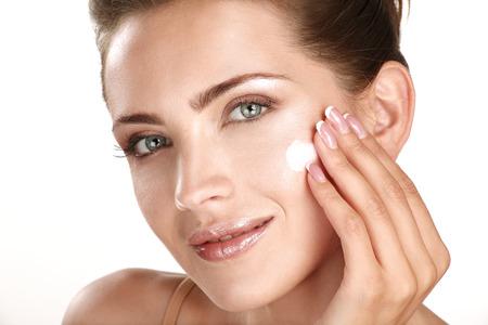 bella modelo treatmen aplicar crema cosmética en la cara en blanco