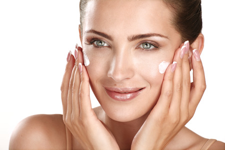 woman face cream: beautiful model applying cosmetic cream treatmen on her face on white Stock Photo