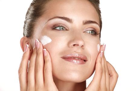 美しいモデルのホワイトに彼女の顔に化粧品クリーム アプローチを適用します。