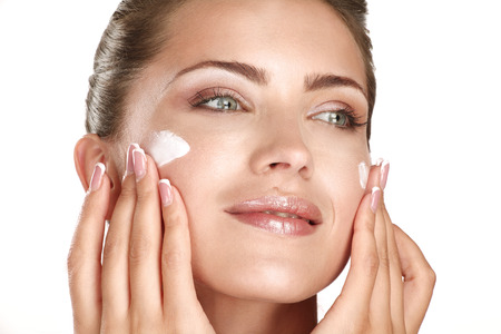 beautiful model applying cosmetic cream treatmen on her face on white Banque d'images