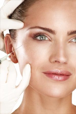 joven y bella modelo inyección de un tratamiento cosmético en blanco