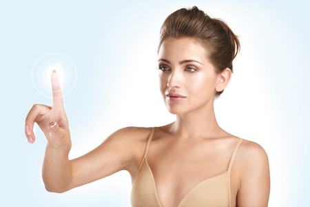 young beautiful model touching a futuristic screen panel on neutral background photo