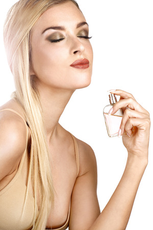 elegant woman applying perfume on her body on white photo