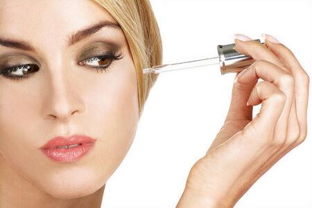 serum: beautiful model applying a skin serum treatment on white Stock Photo