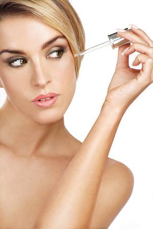 esthetician: beautiful model applying a skin serum treatment on white Stock Photo