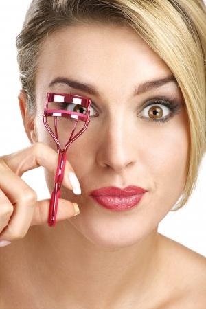 close up of a funny beautiful girl using eyelash curler on white Standard-Bild