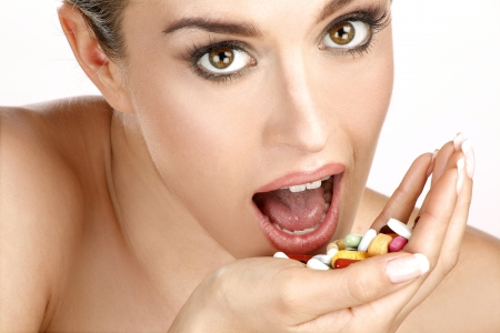 close up of a beautiful girl having pills on white