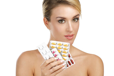 beautiful girl showing many differents medicines on white photo