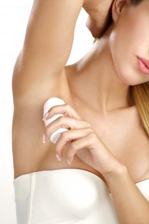 hermosa mujer de aplicar el desodorante roll on white Foto de archivo