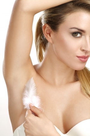 depilation: beautiful woman showing her perfectly shaved armpit on white