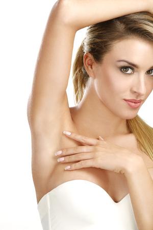 axila: hermosa mujer mostrando su axila perfectamente afeitado en blanco Foto de archivo