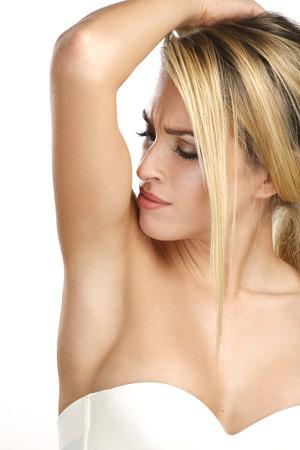 beautiful woman applying roll deodorant on white photo