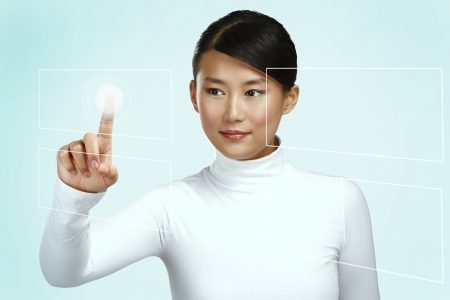 Young asian woman working on a futuristic touchscreen on neutral background photo