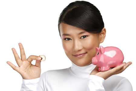Beautiful happy chinese girl showing a piggybank on white photo