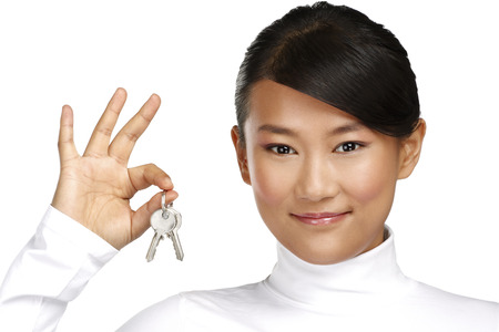 Cute asian chinese girl showing flat keys on white photo