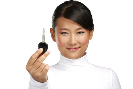 test drive: happy asian chinese woman giving key car on white