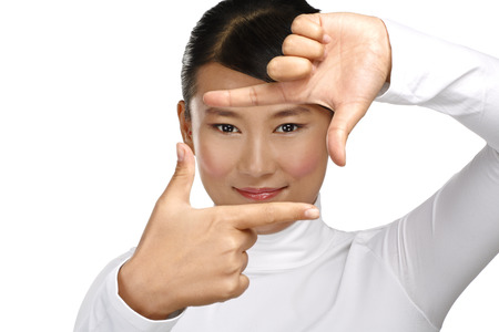 Beautiful asian woman make a frame shot symbol with her hands on white