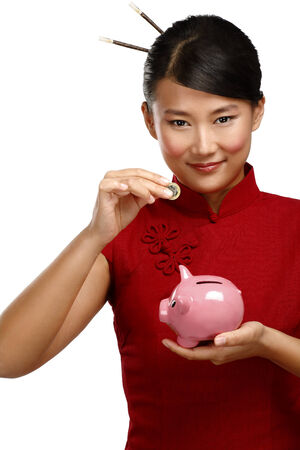 Traditional asian woman save a coin in a piggybank on white photo