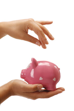 Female hands holding a piggybank empty space to insert a coin on white photo