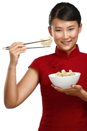 Mujer china que muestra la comida asiática utilizando los palillos en blanco Foto de archivo